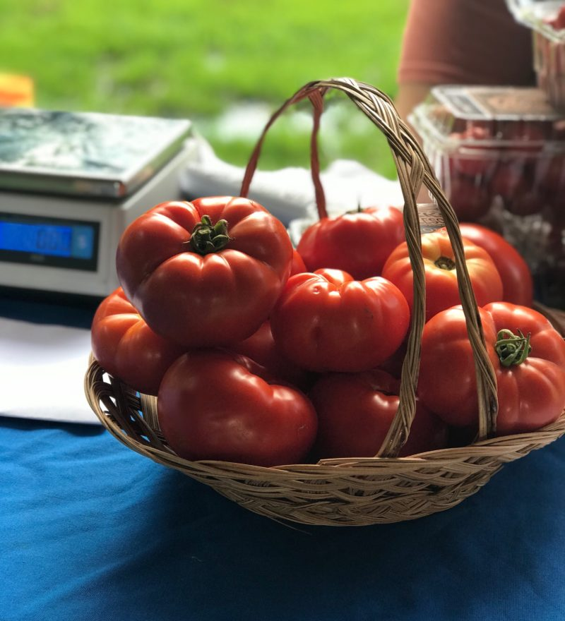 Ripe tomatoes in a basket on a blue tablecloth with a scale in the background.